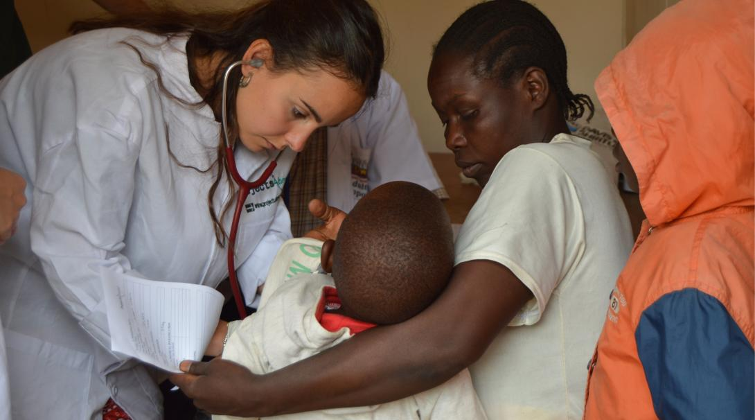 On a summer opportunity for medical students abroad, a Tanzanian child is examined by an elective student
